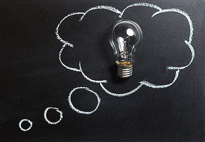 Idee, ein Licht geht auf. Zeichnung und Fotografie einer Glühbirne in einer Denkwolke.