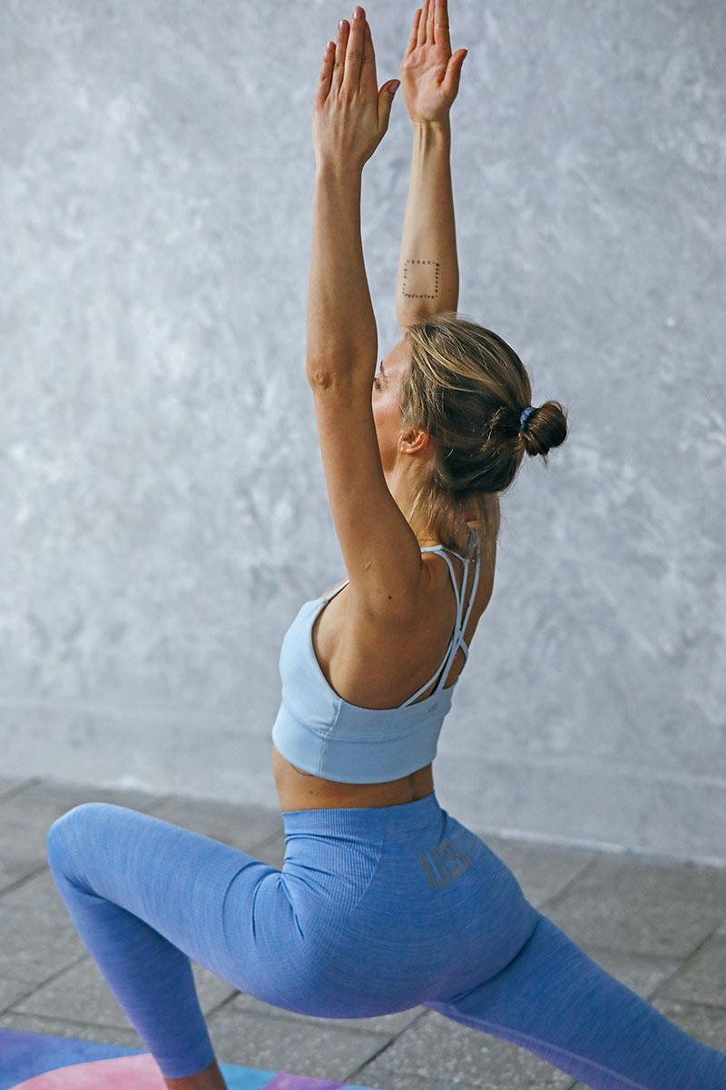 Frau in blauer Sportkleidung beim Yoga